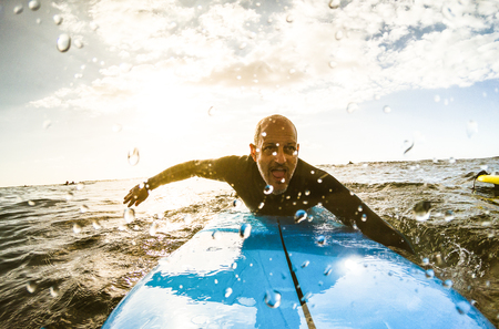 Surfer guy paddling with surfboard at sunset in Tenerife with unrecognizable people at surf boards on background - Sport travel concept with shallow depth of field with drops on lens as composition Stock Photo