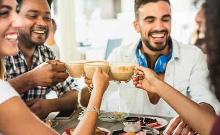Groupe d'amis buvant un café au lait au café-bar - Des gens discutent et s'amusent à la cafétéria de la mode - Concept d'amitié avec des hommes et des femmes heureux au café - Zoom sur les tasses à cappuccino Banque d'images - 94723494