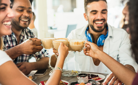 Grupo de amigos bebendo latte no café restaurante bar - pessoas conversando e se divertindo juntos no café de moda - conceito de amizade com homens felizes e mulheres no café - foco em copos de cappuccino Foto de archivo