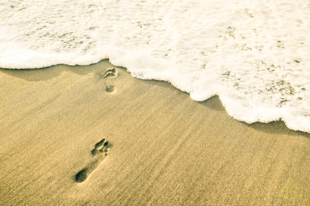 Footprints of naked barefoot at beach against upcoming wave foam from the sea - Freedom and wanderlust summer travel concept on warm contrasted sunset filter