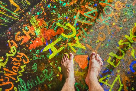 Naked human barefoot on fluo neon painted floor at full moon beach party in Thailand - Travel wanderlust concept with bare feet of guy having fun at event concert nightlife Stock Photo - 94723497