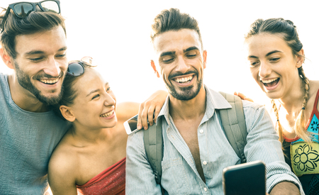 Friends group having fun using mobile smart phone - Technology addiction concept in youth lifestyle sharing content on social network - Always connected people on smartphone - Vintage backlight filter 写真素材