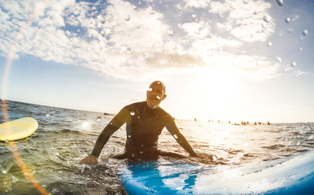 Guy surfer relaxing on surfboard at sunset in Tenerife with unrecognizable people at surf boards on background - Sport travel concept with shallow depth of field with drops on lens as composition