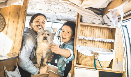 Hipster couple with cute dog traveling together on oldtimer mini van transport - Travel lifetstyle concept with indie people on minivan adventure trip having fun in relax moment - Vintage retro filter