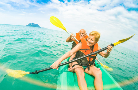 Senior happy couple taking travel selfie on kayak at Ang Thong marine park in Ko Samui - Trip to Thailand wonders - Active elderly concept around world - Tilted composition and sunshine flare filter