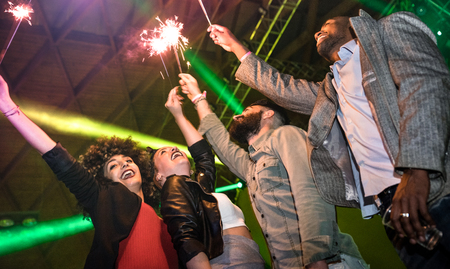 Multiracial young friends dancing at night club with sparkler fireworks - Happy people having crazy fun at nightclub after party - Nightlife drunk concept with guys and girls at concert festival event Фото со стока