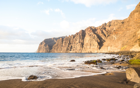 Desert solitary beach in Tenerife with Los Gigantes cliffs on background - Travel concept with nature wonder landscape in Canary islands Spain - Bright warm afternoon filtered color tones