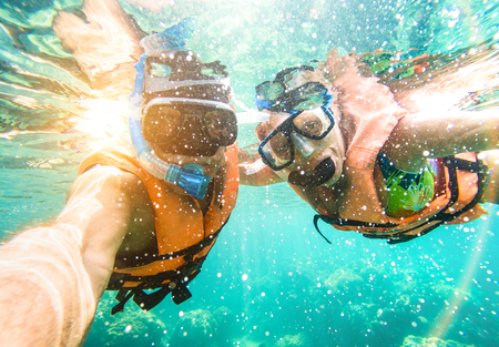 Senior happy couple taking selfie in tropical sea excursion with water camera - Boat trip snorkeling in exotic scenarios - Active retired elderly and fun concept on scuba diving - Warm vivid filter Stockfoto