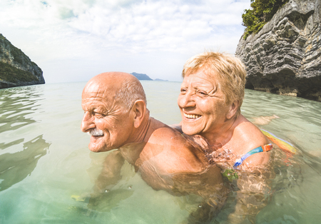 Senior couple vacationer having genuine playful fun on tropical beach in Thailand - Snorkel tour in exotic scenario - Active elderly and travel concept around the world - Warm afternoon bright filter Imagens - 96392393