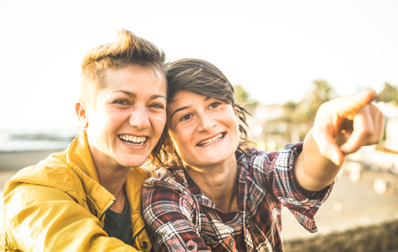 Happy girlfriends in love sharing time together at travel trip pointing on horizon - Women friendship concept with girls couple having fun on fashion clothes outdoors - Bright warm sunset filter Archivio Fotografico