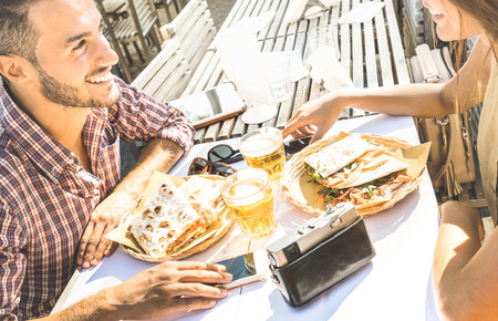 Couple in love having fun at street food restaurant on travel excursion - Young happy tourists enjoying happy moment at beer bar - Relationship concept with focus on guy face and warm bright filter