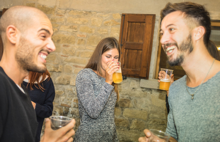 Happy friends drinking beer at house birthday party - Friendship concept with people having fun together - Young men sharing joy moment celebrating at home - Warm filter with focus on middle girl