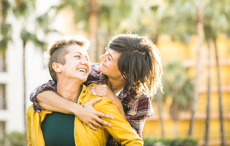 Happy playful girlfriends in love sharing time together at travel trip on piggyback hug - Women friendship concept with girls couple having fun on fashion clothes outdoors - Bright warm sunset filter Banque d'images