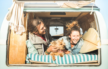 Hipster couple with cute dog traveling together on vintage mini van transport - Life inspiration concept with hippie people on minivan adventure trip in relax moment - Bright warm retro filter Stockfoto