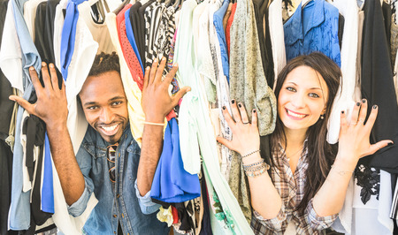 Young multiracial couple having fun at clothing flea market - Best friends sharing time shopping on cheap sale - Lovers enjoying everyday life moments - Wardrobe fashion shop concept with happy people 스톡 콘텐츠
