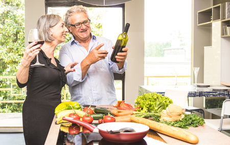 Senior couple cooking healthy food and drinking red wine at house kitchen - Retired people at home preparing lunch with fresh vegetables and bio products - Happy elderly concept with mature pensioner Banque d'images