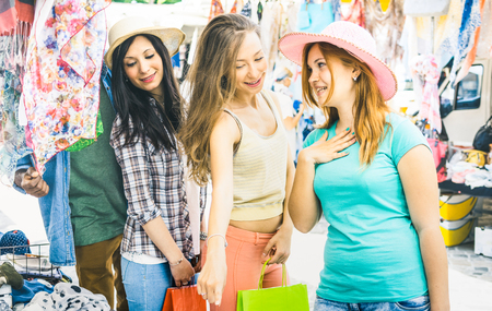 Young pretty women girlfriends at cloth flea market looking for fashion wardrobe - Friendship concept with female best friends having fun and shopping in old town - Bright vintage color tones filter Imagens