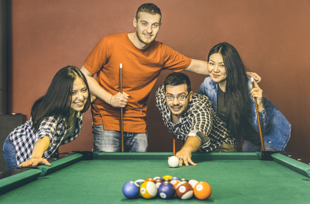 Young friends playing pool at billiard table saloon - Happy friendship concept with fashion people having fun together and sharing time at snooker gameroom - Warm vintage retro contrast filter Banque d'images