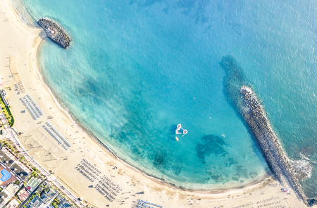 Widok z lotu ptaka na plażę w zatoce Los Cristianos na Teneryfie z miniaturowymi leżakami i parasolami - Koncepcja podróży z krajobrazem cudów natury na Wyspach Kanaryjskich w Hiszpanii - Filtr jasny, ciepły dzień Zdjęcie Seryjne