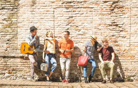 Group of happy excited friends having fun outdoor cheering with guitar - Young people enjoying spring summer time together at city town tour - Youth friendship concept on warm afternoon color filter Stock Photo