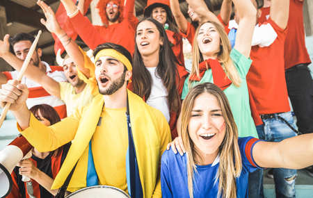 Young football supporter friends cheering and watching soccer cup match at intenational stadium - People fans group with multicolored t-shirts having excited fun on sport world championship concept