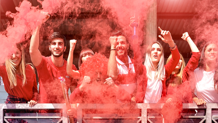 Young football supporter fans cheering with colored smoke watching soccer match together at stadium - Friends people group with red t-shirts having excited fun on sport world championship concept Foto de archivo