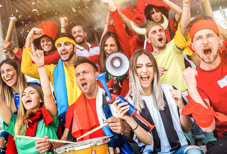 Football supporter fans friends cheering and watching soccer cup match at intenational stadium - Young people group with multicolored t-shirts having excited fun on sport world championship concept Imagens - 100259965
