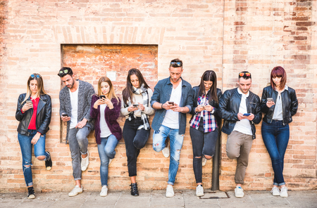 Friends group using smartphone against wall at university college backyard break - Young people addicted by mobile smart phone - Technology concept with always connected millennials - Filter image Stock Photo - 100159812