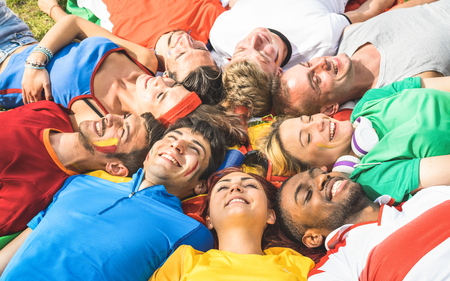 Happy friend group lying on meadow after world soccer event - Friendship concept with young people having fun at international sport festival - Football cup championship concept on warm bright filter