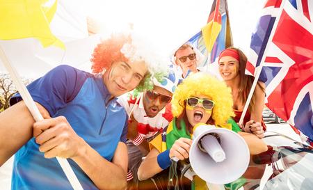 Kibice kibiców piłki nożnej przyjaciele kibicujący po meczu piłkarskim kręcący się z samochodem i flagami - grupa młodych ludzi z wielokolorowymi koszulkami, podekscytowana zabawą na mistrzostwach świata w sporcie Zdjęcie Seryjne