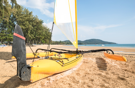 Small catamaran sailboat on the shore - Water sport race concept with technical equipment at beach - Sailing boat vessel ready to challenge the wind Stock Photo