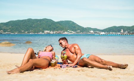 Young couple vacationer having genuine fun on tropical Phuket beach in Thailand with coconut drink - Active youth love and travel concept around world - Bright warm color filter tones