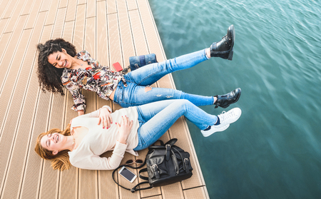 Happy multiracial girlfriends having genuine fun at jetty pier docks - Friendship concept with girls at spring break travel - Modern lifestyle with female best friends women - Warm bright filter tone