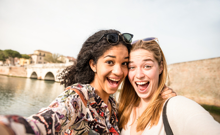 Happy multiracial girlfriends taking selfie and having fun outddors - Friendship concept with girls at spring break travel - Modern lifestyle with female best friends women - Bright day filter tone Stock Photo