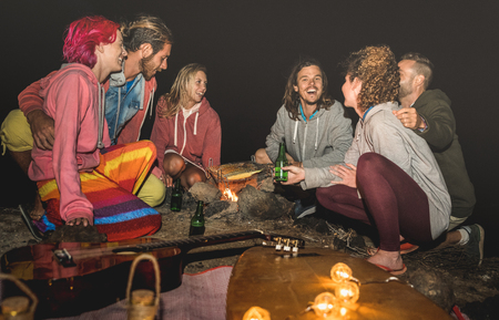 Young hippie friends having fun together at beach camping party with night campfire bbq- Friendship travel concept with young surfer people grilling corn cob at summer barbecue - High iso image