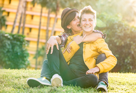 Happy girlfriends in love sharing time together at travel trip hugging at garden - Playful women friendship concept with girls couple having fun on fashion clothes outdoors - Bright warm sunset filter