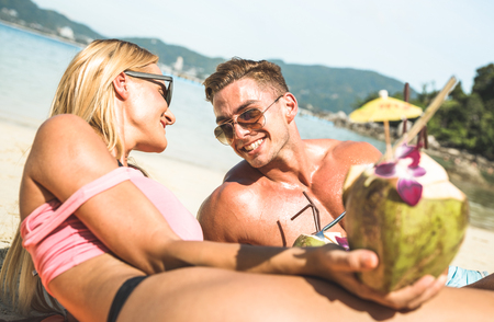 Portrait of young couple vacationer having fun on tropical Phuket beach in Thailand with coconut drink - Active youth and travel concept with people in love around the world - Bright warm filter tones