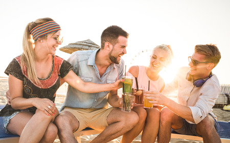 Group of happy millenial friends having fun at beach party drinking cocktail at sunset - Summer joy and friendship concept with young people on vacation - Warm sunshine filtered color tones