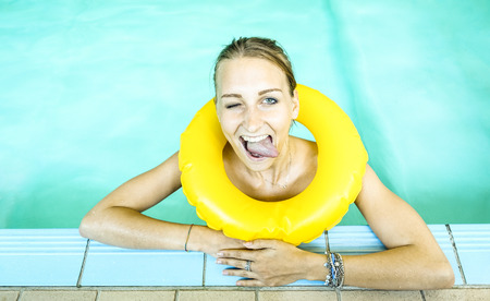 Happy woman in clear water looking at camera with bigmouth expression - Young girl at swimming pool class with life buoy - Medical concept of hydrotherapy spa treatment and swim school - Azure filter Archivio Fotografico