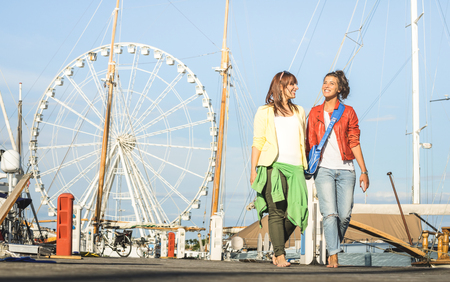 Young women girlfriends walking together on public jetty pier docks with ferris wheel on background - Best female friends traveling on european summer destinations - Warm bright saturated filter Stock Photo