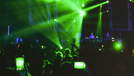 Blurred people dancing at music night festival event - Abtsract defocused image background of disco club after party with laser show - Nightlife entertainment concept - Bright green spotlight filter