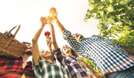 Freunde, die Rotweinglas in den Himmel rösten und Spaß haben, bei Sonnenuntergang-Hintergrundbeleuchtung zu jubeln - junge Leute, die Erntezeit zusammen auf Bauernhof-Weinberglandschaft genießen - Jugend- und Freundschaftskonzept