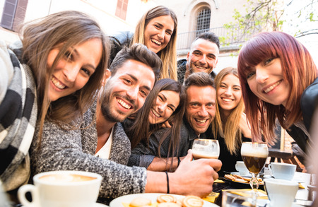 Friends taking selfie at bar restaurant drinking cappuccino and irish coffee - People having fun together at fashion cafeteria - Friendship concept with happy men and women at cafe - Warm filter