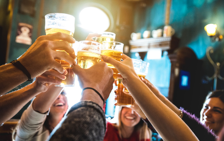 Group of happy friends drinking and toasting beer at brewery bar restaurant - Friendship concept with young people having fun together at cool vintage pub - Focus on middle pint glass - High iso image Foto de archivo