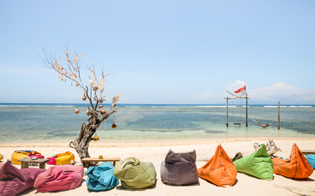 Gili Trawangan beach on a sunny day with multicolored sofas at chilling lounge - Travel and vacation concept with beautiful destinations worldwide - Bali and Lombok environments in Indonesia islands Stock Photo