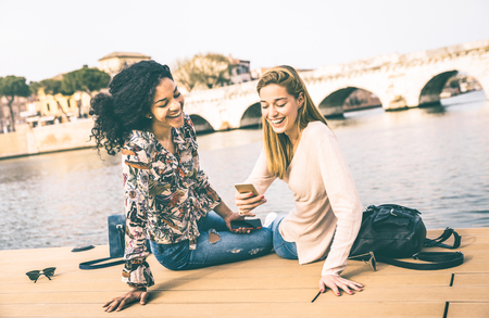 Happy multiracial girlfriends having fun with mobile smart phone at park - Friendship concept with girls at wandering travel - Modern female lifestyle with women best friends - Vintage contrast filter