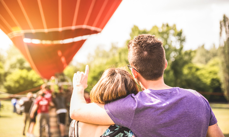 Happy couple in love on honeymoon excursion waiting for hot air balloon ride - Summer travel concept with young people travelers having fun at trip vacation - Bright warm filter with backlight Stock Photo