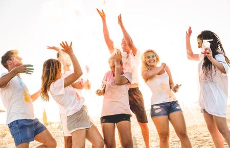 Groupe d'amis heureux s'amusant à la fête sur la plage le festival d'été de couleurs holi - Les jeunes rient ensemble avec une véritable humeur insouciante - Concept de jeunesse et d'amitié avec de la poudre multicolore