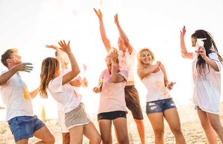 Group of happy friends having fun at beach party on holi colors summer festival - Young people laughing together with genuine carefree mood - Youth and friendship concept with multi colored powder