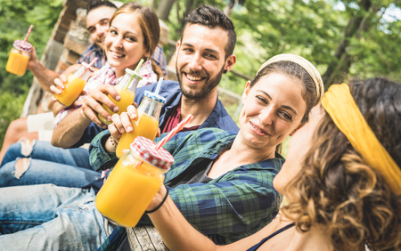 Happy friends drinking healthy orange fruit juice at countryside picnic - Young people millennials having fun together outdoors on afternoon snack at garden -  Friendship concept in nature environment Stock Photo